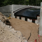 Bridge backfill and barrier membrane installed