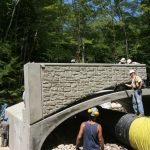 Installing the curb walls of the bridge with an Ashlar Stone finish