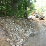 Installing Class C Stone to the extremely steep roadside slopes